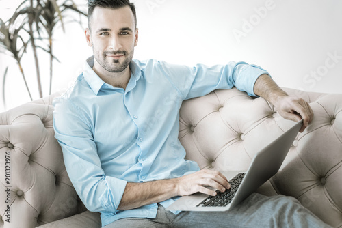 Foto Murales Busy day. Appealing positive male freelancer working on laptop while looking at camera and posing on sofa