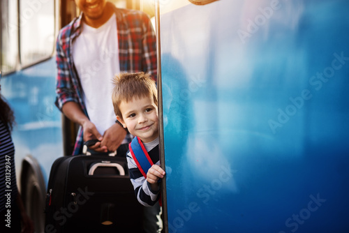 Fototapeta Little cheerful boy is peaking outside the blue bus while a young man is looking at him and smiling.