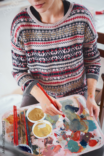 Foto Murales Woman artist painting on canvas in her atelier