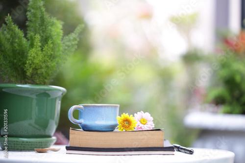 Błękitna rocznik filiżanka, kwiat z notatnikami przy plenerowym i