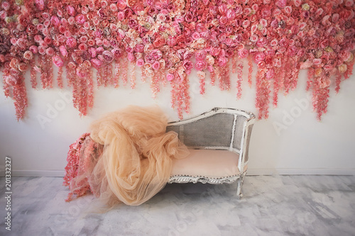 Stara rzeźbiona kanapa z miękkim obiciem na białej ścianie ozdobiona różowymi kwiatami. Wspaniała girlanda. Wystrój wnętrza to romantyczna strefa ślubna.