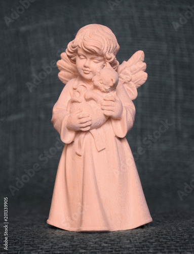 A wooden sculpture of a small angel with a cat on his hands. It was bought in a souvenir shop in Oberammergau (Germany). Russia, March, 2018. - 201339905