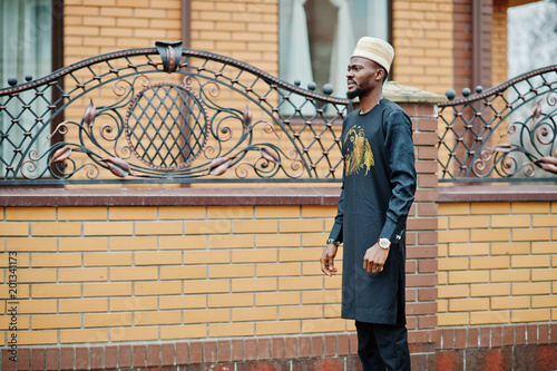 Rich african man in stylish traditional clothes and hat posed outdoor background his mansion.