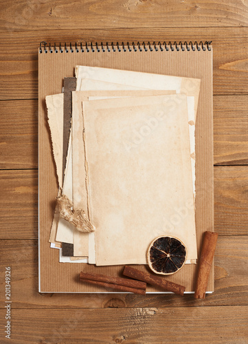 Foto Murales old sheet of paper on wooden background, spice and decoration, top view, retro style