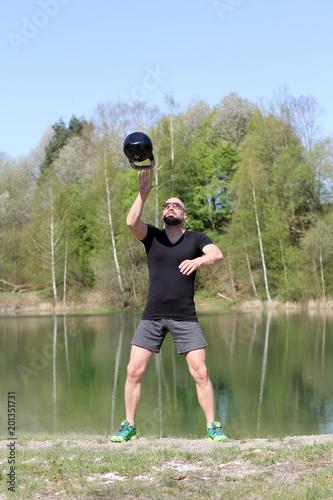 Poranne ćwiczenia z kettlebells nad jeziorem