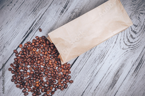 Wall mural Coffee beans in a kraft paper bag on a wooden table
