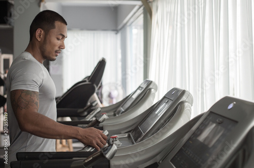 Poster Muscular builder man running in machine treadmill at fitness gym club