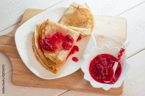 Pancakes with raspberry jam on a white plate stand on a natural wooden Board and a light wooden table  - 201366131