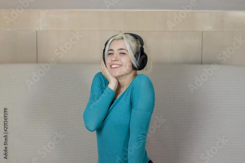 Szczęśliwy blondynki młodej kobiety obsiadanie na kanapie z hełmofonami słucha muzyka w domu