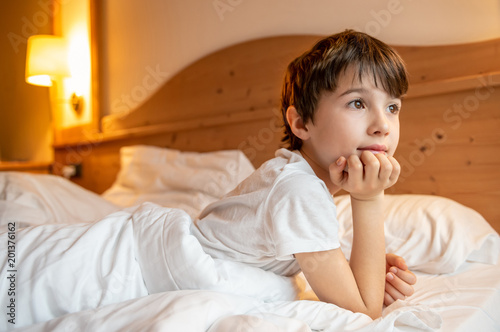 Child leaning on the pillow waking up to the light that filters through the window