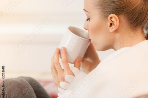 Wall mural Woman lying on sofa under blanket drinking tea