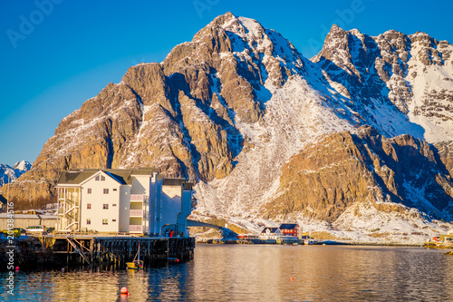 Outdoor view of a white building in the shore with a huge mountaing behind in Henningsvaer on Lofoten islands - 201384516