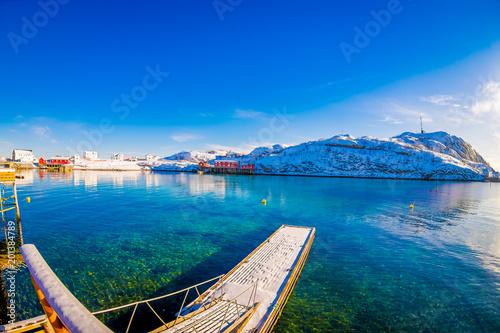 Odkryty widok niesamowity krajobraz przyrody z turkusową wodą i słoneczny dzień w błękitne niebo z pływającą strukturą w jeziorze i ogromną górą pokryte śniegiem w Svolvær
