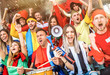 Leinwandbild Motiv Football supporter fans friends cheering and watching soccer cup match at intenational stadium - Young people group with multicolored t-shirts having excited fun on sport world championship concept