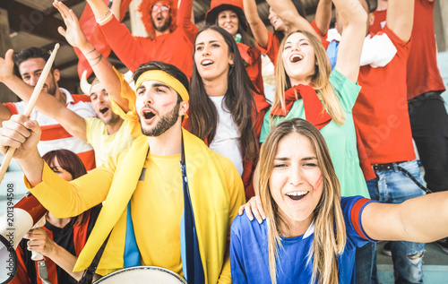 Foto Murales Young football supporter friends cheering and watching soccer cup match at intenational stadium - People fans group with multicolored t-shirts having excited fun on sport world championship concept
