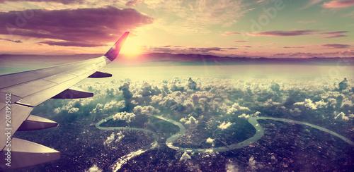 Pojęcie samolotowa podróżować Latający nad miastem w kierunku miejsca przeznaczenia. Zachód słońca krajobraz nad chmurami.