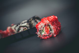 Fototapeta Maki - Red sushi roll and plastic plate with rolls on a black background © Igor