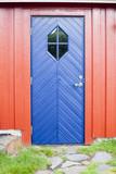 Puerta azul en pared de madera roja - 201408913