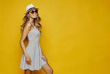 Cheerful and smiling blonde model sexy girl with perfect body, in white striped fitting dress, hat and sunglasses, posing sideways, isolated at yellow background - 201417353