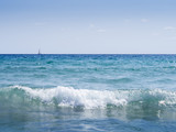 ocean waves with sailing ship on the horizon
