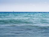 ocean scene with sailing ship on the horizon