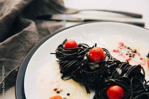 Czarny spaghetti z pomidorami w talerzu. Śródziemnomorskie pyszne jedzenie.