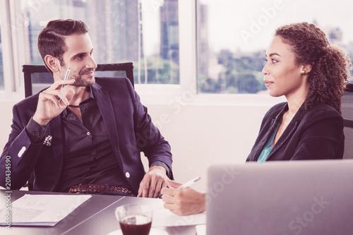 Uśmiechnięty biznesmen patrzeje jego żeńskiego kolegi przy spotkaniem w biurze