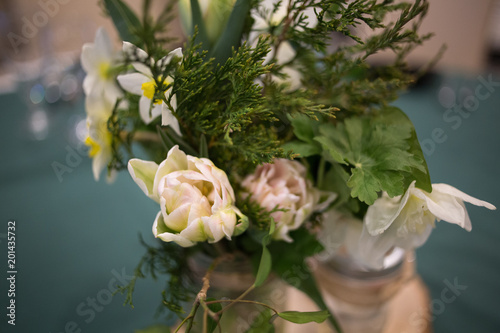 Żółty i biały kwiatek wiosna w szklanym puszce słoik na drewnianej płycie