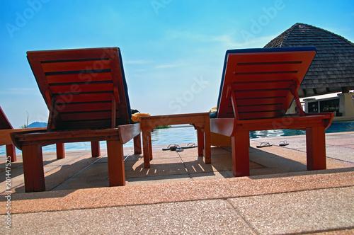 Foto Murales Concept of lifestyle in a tropical resort. Sun loungers by the pool. Bottom view.