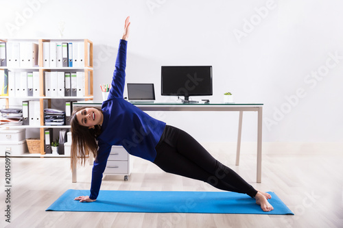 Foto Murales Businesswoman Doing Exercise On Exercise Mat