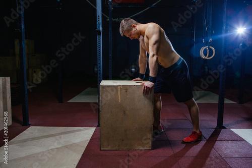 Portret zmęczony facet fitness. W pobliżu drewnianej kostki. Styl dopasowania krzyża.