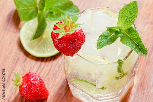 Szklanka zimnej wody z cytryną i limonką, kostkami lodu i listkami mięty