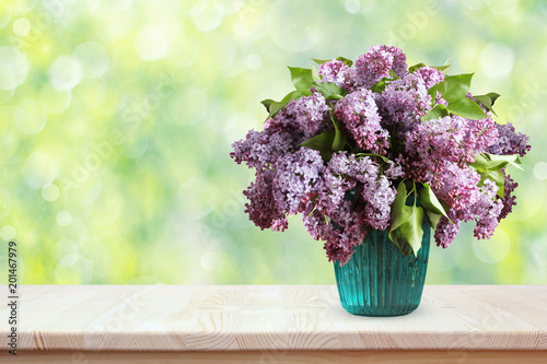 Bouquet of lilacs on a wooden table. Flowers in a vase.
