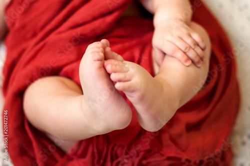 Child feet on white blanket on bed