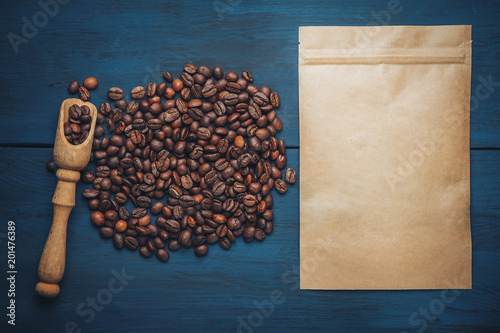 scattered coffee beans from kraft packaging on a blue, wooden background, top view