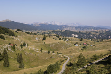Hilly landscape with houses and a street in Durmitor National Park in Dinaric Alps, Montenegro