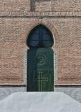 Puerta neomudejar. Puerta de arco de herradura en hierro verde sobre fachada de ladrillo de la iglesia de san Matías en Madrid. España - 201481798