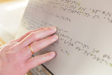 Hand of a blind person reading some braille text touching the relief. - 201485903