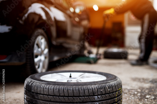 New tire laying on the pavement near the mechanic ready to replace the one on a car.