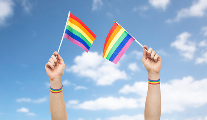 lgbt, same-sex relationships and homosexual concept - close up of male hand wearing gay pride awareness wristbands holding rainbow flags over blue sky and clouds background