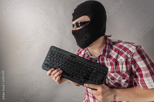 Foto Murales Man wearing balaclava shooting from keyboard