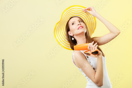 Woman in summer hat holds sunglasses sunscreen lotion