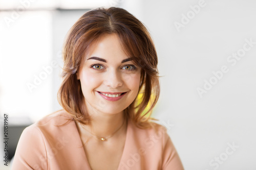 people, emotion and facial expression concept - portrait of happy smiling young woman