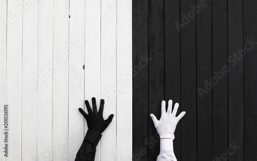 Ręki w czarny i biały rękawiczkach na czarny i biały tle