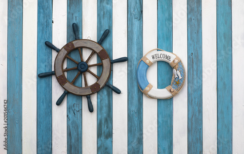 Canvas Schip old wooden ship steering wheel on a blue white wooden background