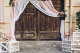 rustic wedding photo zone. wooden barn doors with fabric and white boxes with flowers and candles at stylish wedding photo booth. shabby chic. luxury arrangements - 201548793