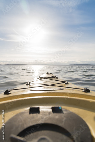 Aluminium Schipbreuk Point of view yellow kayak at sea pointed at the setting sun vertical.