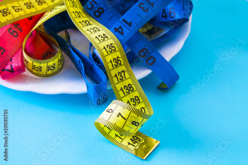Foto Murales plate with colored tape measures. diet and slimming concept