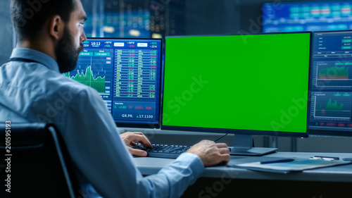 Over the Shoulder View of Stock Market Trader Working on a Computer with Isolated Mock-up Green Screen and Second Display Showing Number Ticker with Graphs.