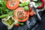 Delicious Salmon rolls, goats cheese in paper with knife, aromatic herbs, spices and rosemary oil in wave glass on old black stone background, clean eating, healthy food, diet or cooking concept - 201597509